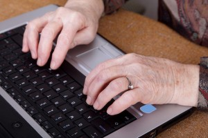 Active retirement senior womans hands and lap top